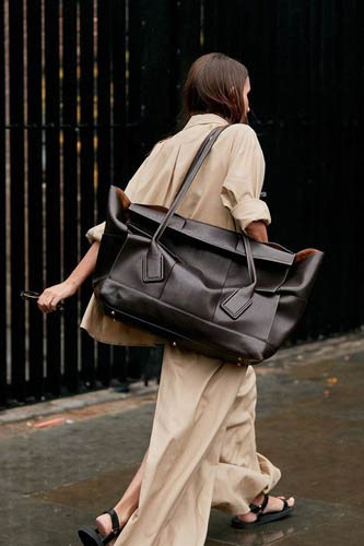 street style shoot of blogger wearing baggy cream outfit and massive brown leather bag